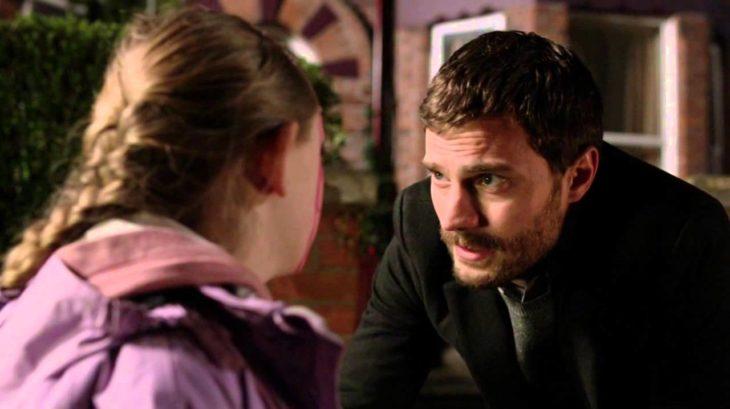 Jamie Dornan en su papel de the fall conversando con una niña