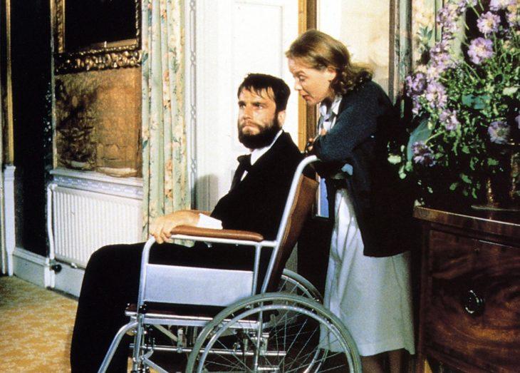Actor de mi pie izquierdo postrado en una silla de ruedas y empujado por una mujer