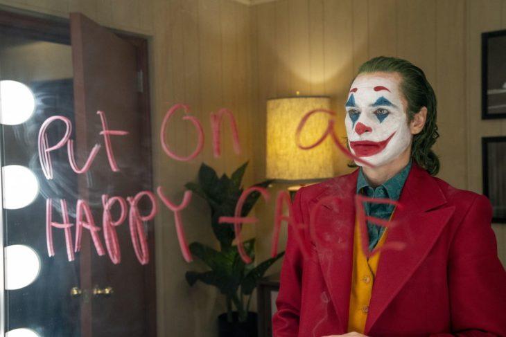 Actor Joaquin Phoenix en la película The Joker, mirándose frente a un espejo