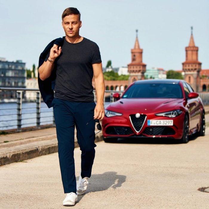 Actor Alemán posando en una sesión de fotos frente a su automóvil