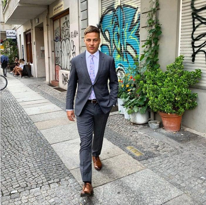 Actor Alemán usando un traje mientras camina por la calle