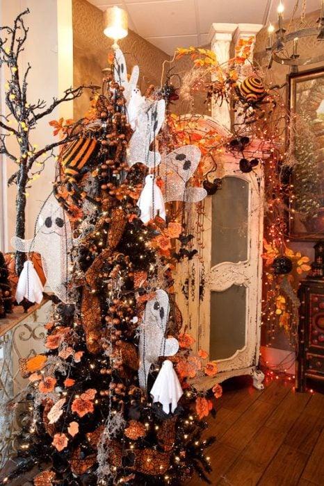 Pino navideño con ramas oscuras con decoración de fantasmas y calabazas