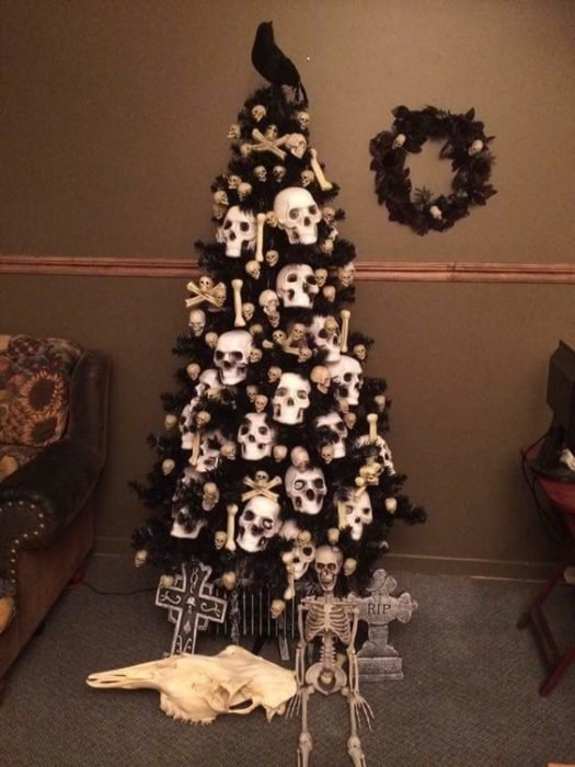 Pino de Navidad con ramas oscuras, accesorios de calaveras, velas blancas y luces
