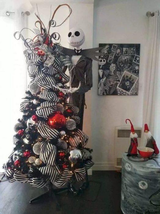 Pino navideño con ramas blancas decorado con esferas rojas y listones anchos