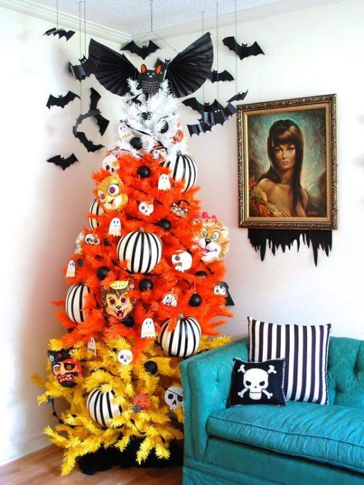 Pino navideño multicolor en amarillo, naranja y blanco decorado con murciélagos