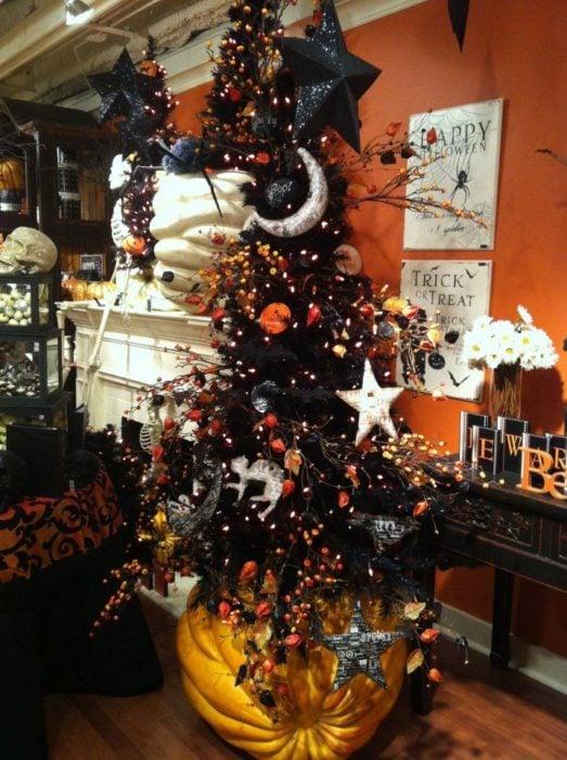 Pino navideño con ramas oscuras decorado con accesorios de Halloween
