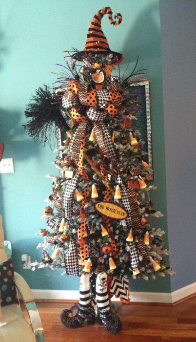 Pino de Navidad decoradocon lsitones cuadrados, naranjas, gorros y dulces de Halloween