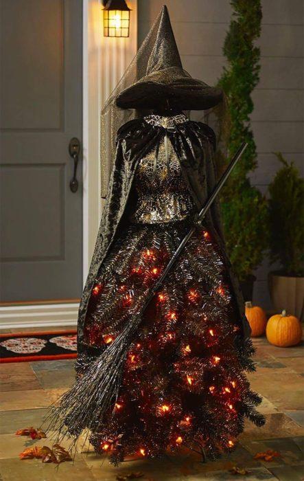 Pino de Navidad decorado con ramas oscuras, luces rojas y accesorios de bruja