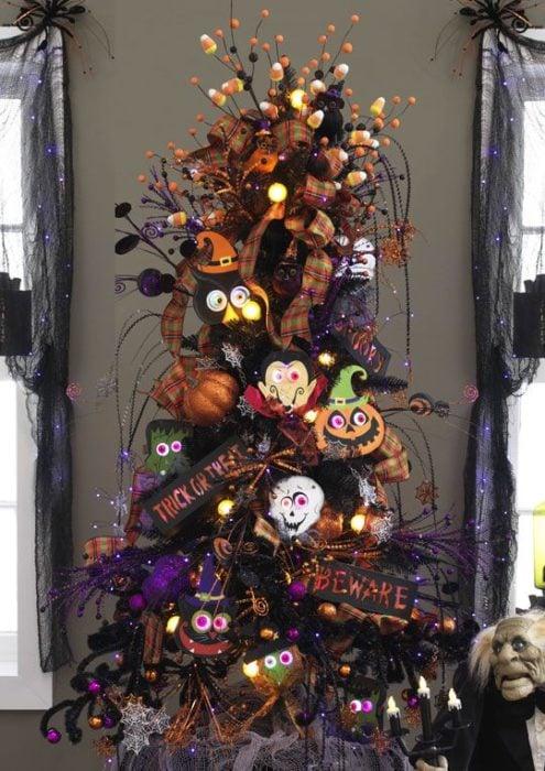 Pino de Navidad con ramas negras decorado con calabazas y accesorios para Halloween