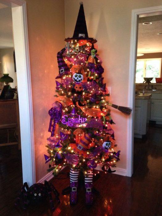 Pino navideño con ramas verdes decorado con calabazas, escobetas y listones morados
