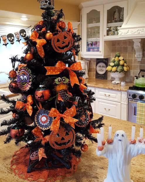 Pino navideño con moños naranjas, calabazas y esferas grandes