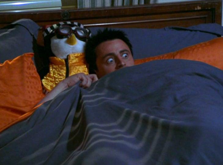 Joey Tribbiani asustado bajo las cobijas con su peluche de pingüino