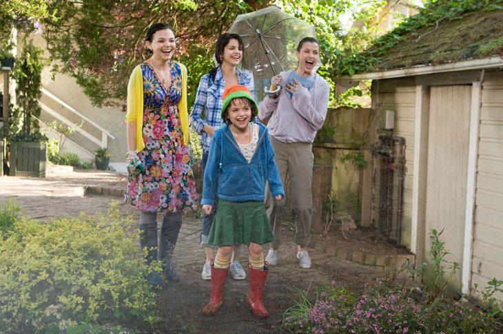 tres mujeres y una niña en un jardín se ríen de algo