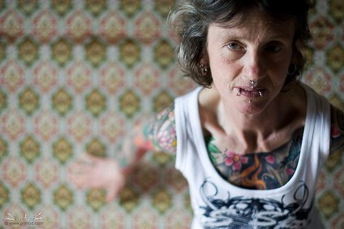 Abuela con tatuajes sentada en el piso