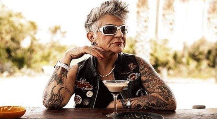 Nonna con le braccia tatuate che beve in un bar