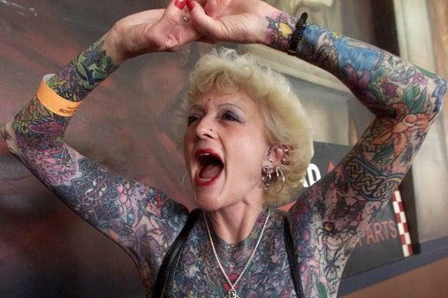 Abuela alzando los brazos llenos de tatuajes y gritando