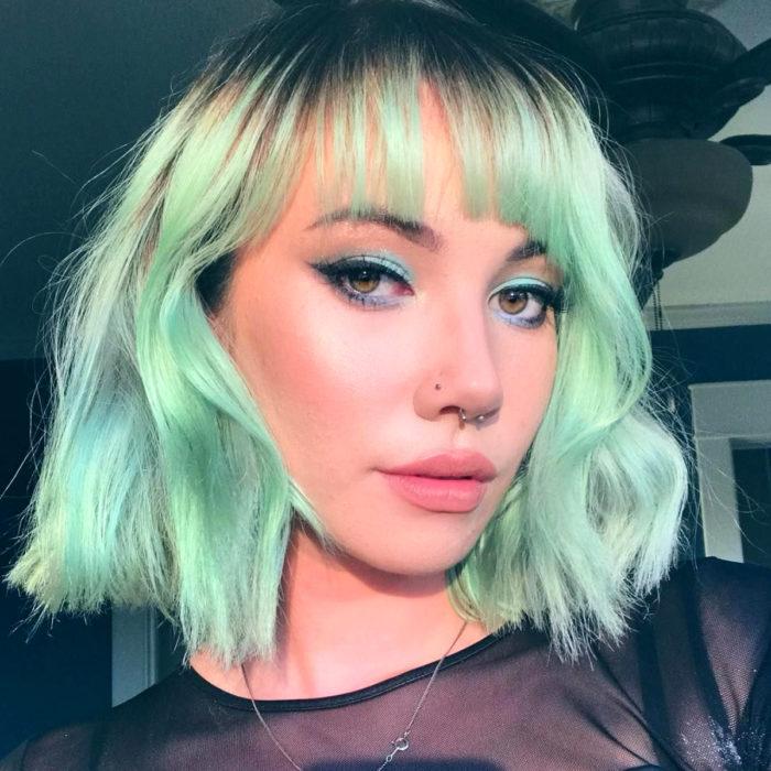 Tinte color verde menta; chica de cabello corto ondulado con fleco, piercings en la nariz y el tabique