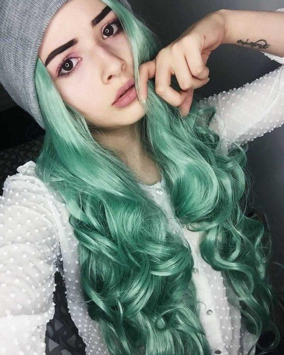 Tinte color verde menta; chica de cabello largo ondulado con gorro