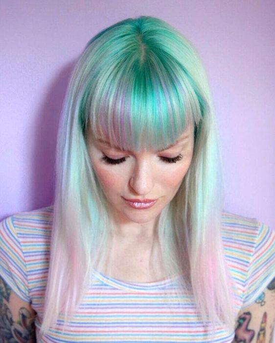 Tinte color verde menta; chica con el cabello verde, rosa y morado, lacio con fleco