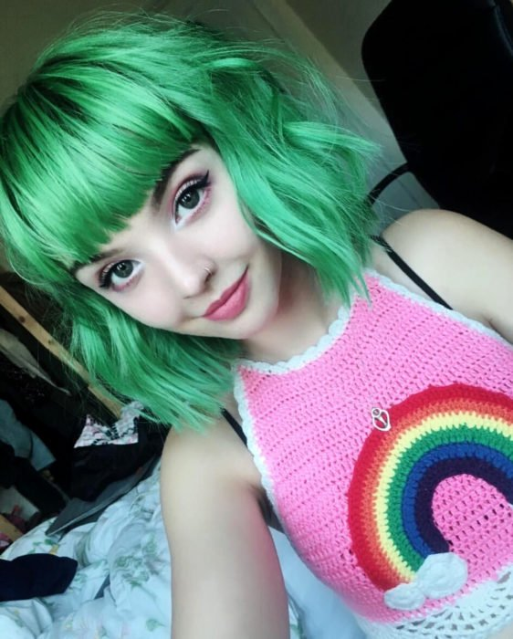 Tinte color verde menta; chica de ojos verdes con crop top tejido con estampado de arcoíris, de cabello corto arriba de los hombros, ondulado con fleco