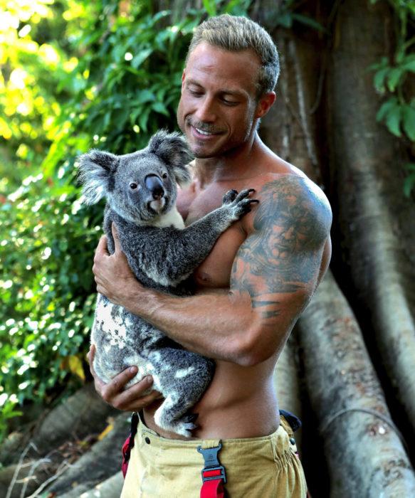 Calendario de bomberos australianos con animales; hombre de ojos azules cargando a un koala