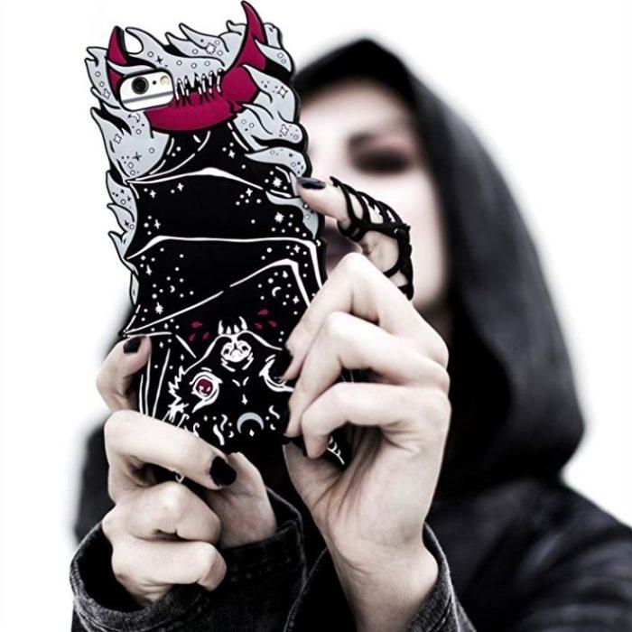 Chica sosteniendo una funda para celular con un murciélago de cabeza