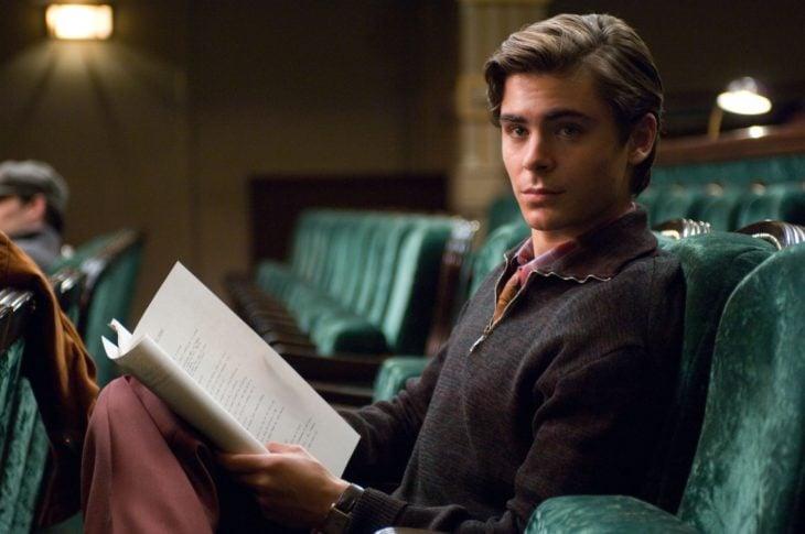Zac Efron sentado en un sofá leyendo