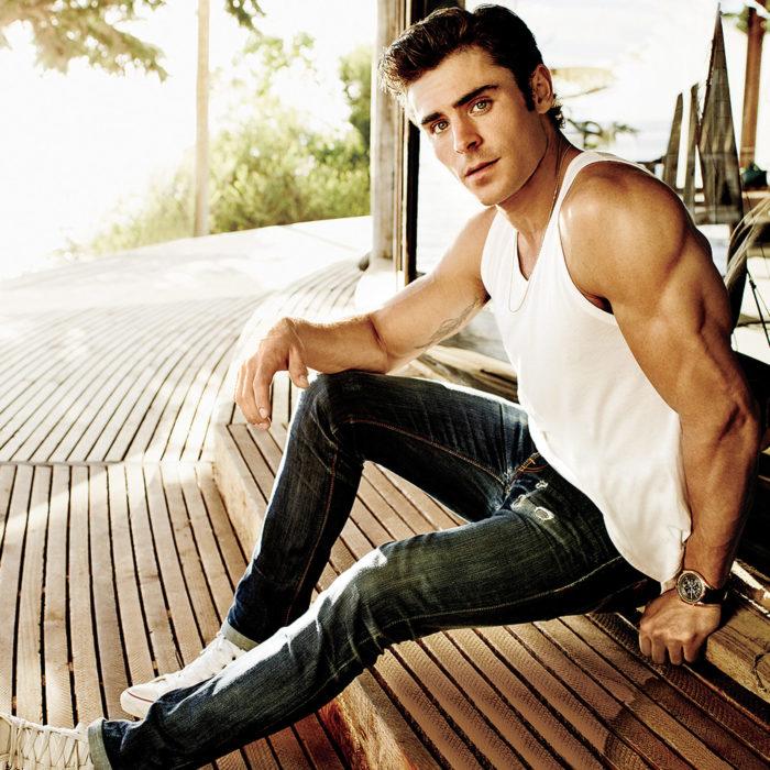 Zac Efron sentado en un banco con camisa de tirantes
