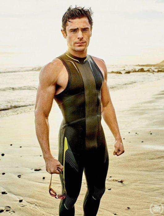 Zac Efron en la playa llevando un traje de neopreno