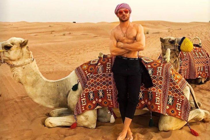 Zac Efron recargado en un camello en el desierto