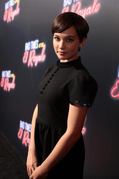 Cailee Spaeny modelando un vestido negro y corto durante una alfombra roja