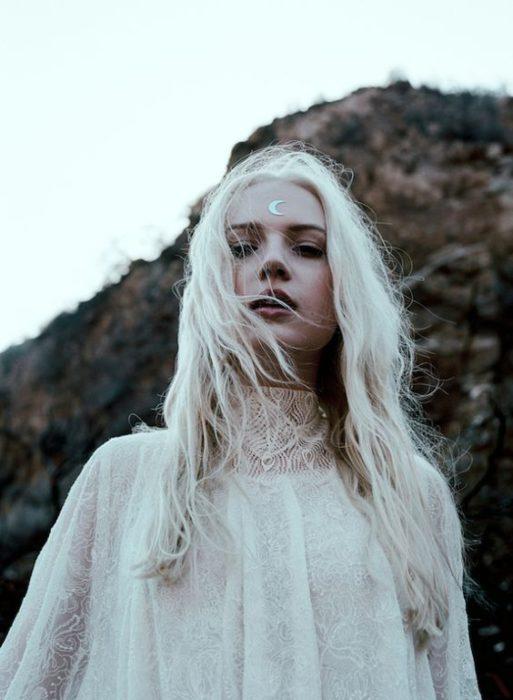 Chica con vestido blanco de encaje, cabello blanco, mirando hacia el cielo