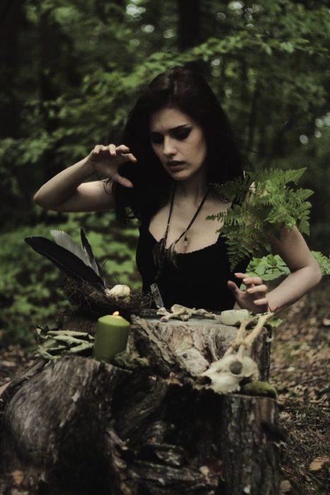 Chica a mitad de bosque, hincada frente a un tronco, alzando los brazos