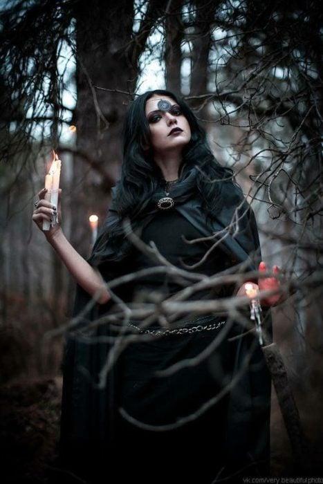 Chica vestida con capa oscura, caminando por el bosque, sosteniendo velas blancas