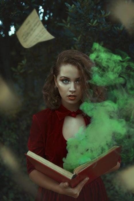 Chica con un libro abierto, hojas volando, humo verde saliendo entre las páginas