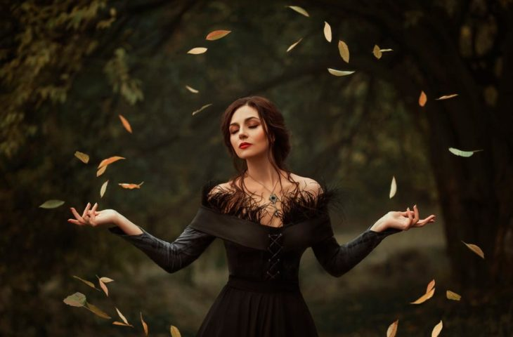 Chica a mitad de bosque alzando hojas con sus manos