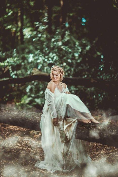 Chica con vestido descubierto al hombro, sentada en un tronco, mirando hacia el agua correr