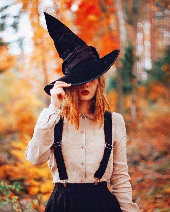 Chica en un bosque repleto de hojas anaranjadas llevando un sombrero de pico