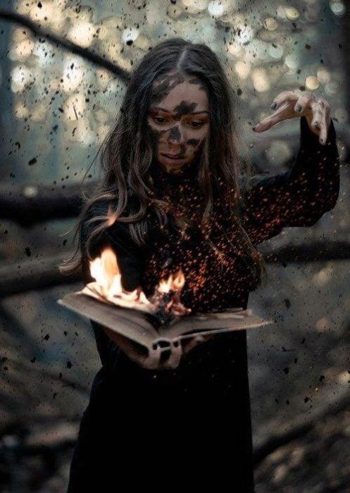Chica en el bosque sosteniendo un libro en llamas