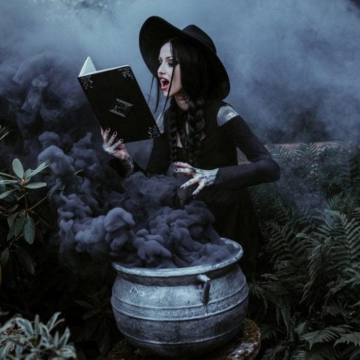 Chica frente a un caldero humeante, leyendo un libro