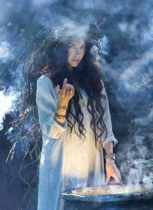Chica parada frente a un caldero en un bosque, vestido blanco de manta, cabello largo