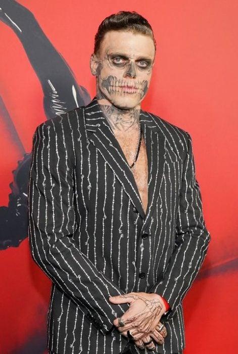 Gus Kenworthyusando un traje a rayas negro con blanco y una pintura en el rostro de calavera
