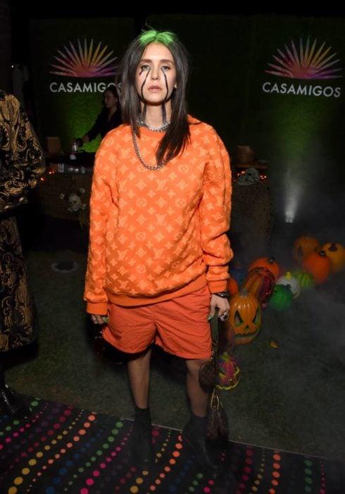 Nina Dobrev disfrazada como la cantante Billie Eilish usando un traje de color naranja