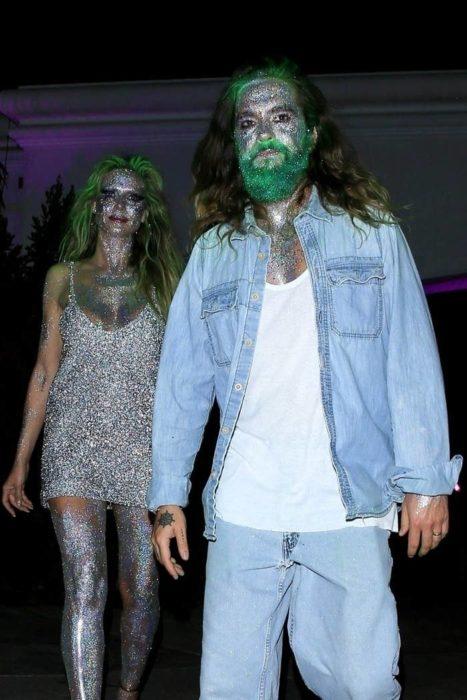 Heidi Klum y Tom Kaulitz caminando tomados de las manos mientras muestran sus disfraces de Halloween cubiertos de brillantina