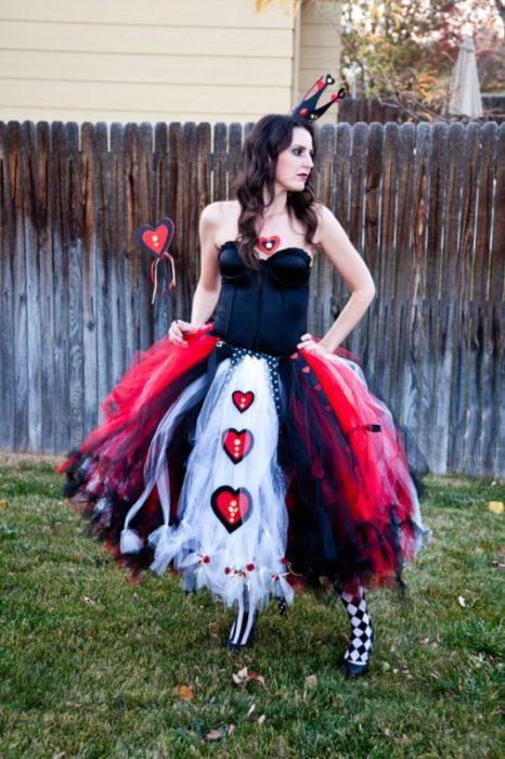 Chica disfrazada como la reina de corazones de Alicia
