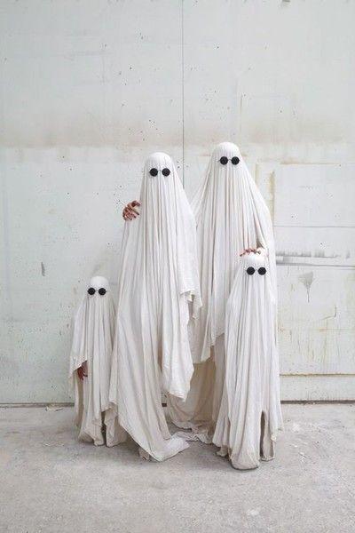 Familia disfrazada como fantasmas con sábanas blancas y ojos negros