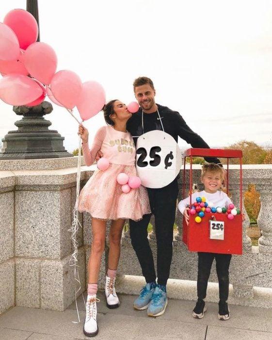 Familia con disfraces de expendedora de chicles y goma de mascar rosa