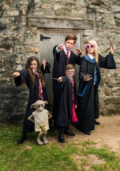 Familia vestida con capas largas y pscuras con diseños de Harry Potter