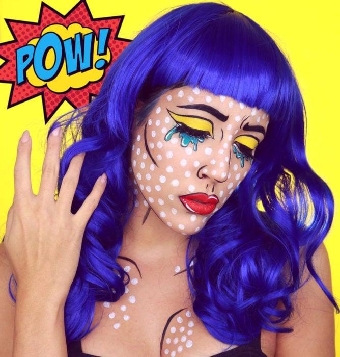 Disfraz de Halloween de comic pop art; chica con peluca azul con peinado ondulado y fleco, maquillada estilo historieta con puntos blancos, sombra amarilla y lágrimas azules