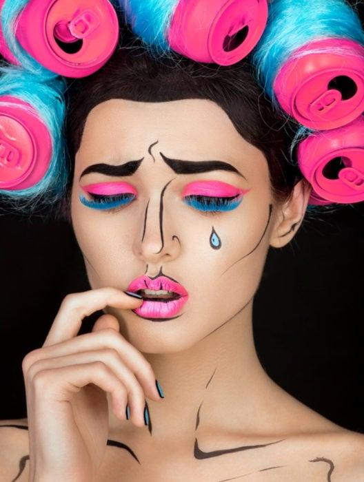 Disfraz de Halloween de comic pop art; mujer maquillada estilo historieta con sombra de ojos fosforescente, lágrimas y latas de refresco como tubos para el cabello